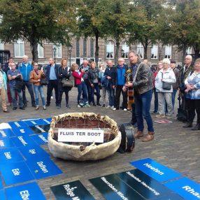 Een man met gitaar zingt een groep demonstranten toe. Op de grond liggen plaatsnaamborden.
