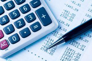 Een rekenmachine en een pen liggen op een financieel overzicht.