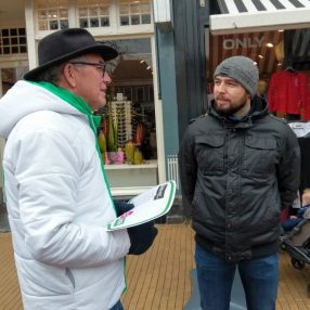 Twee mannen op straat die met elkaar in gesprek zijn.