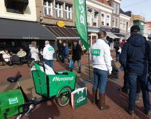 Een groene bakfiets op een markt met daaromheen mensen die in gesprek zijn.