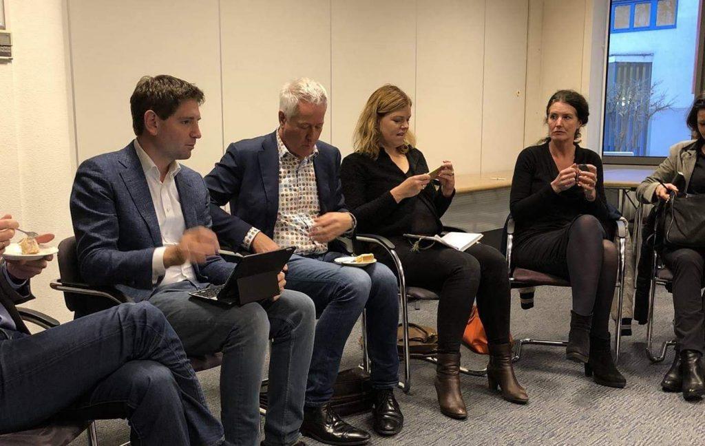 Politici in een kamer in gesprek over Lelystad Airport.