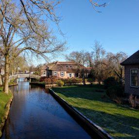 Boerderijen in Giethoorn die aan de gracht liggen met een karakteristieke brug over het water.