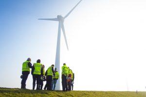 Een windmolen wordt geplaatst op een dijk door bouwvakkers.