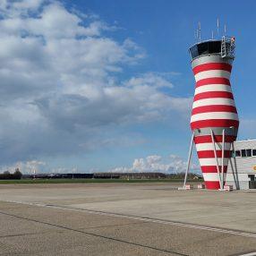 De kenmerkende toren van de luchtverkeersleiding in Lelystad met het vliegveld voor zich.